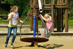 2 Kinder spielen auf einem Spielplatz