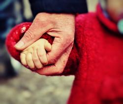 kleine Hand eines Kinder in Hand eines Erwachsenen