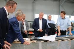 Im Beisein seiner Söhne Mathias und Steve erklärt Geschäftsführer und Inhaber Steffen Weiser (von rechts) der Delegation um Landrat Thomas Fügmann anhand der Baupläne eines der aktuellen Projekte des Unternehmens.