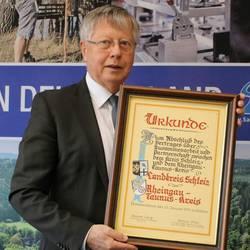 Landrat Thomas Fügmann präsentiert die Urkunde der Kreispartnerschaft