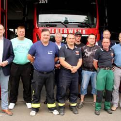 Feuerwehrleute und Vertrete von Stadt und Kreis vor Einsatzfahrzeug Dekon P