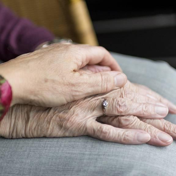 Frau hält Hände eines alten Menschen