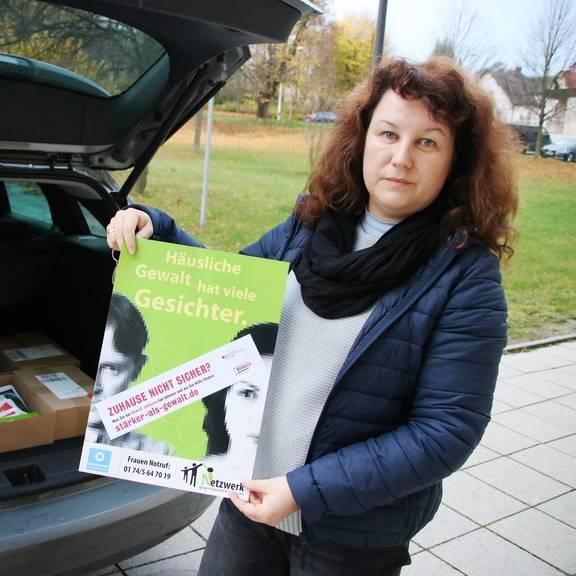 Nadine Hofmann präsentiert zur Aktion gegen häusliche Gewalt Plakate und Flyer