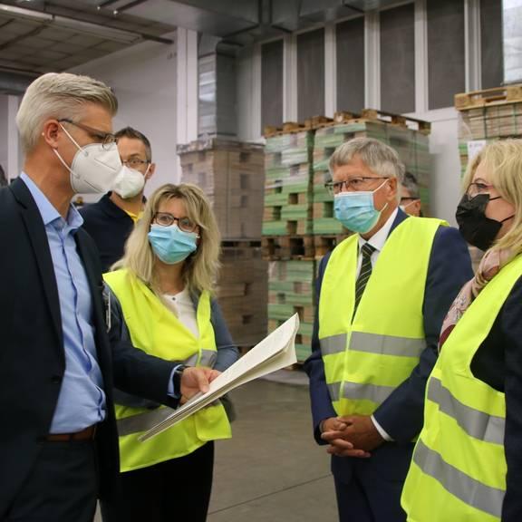 Der neue Geschäftsführer der GGP Media GmbH, Sven Isecke (links), erklärt Landrat Thomas Fügmann (Mitte) und seiner Delegation bei einem Rundgang die wichtigsten Arbeitsschritte bei der Herstellung von Büchern.